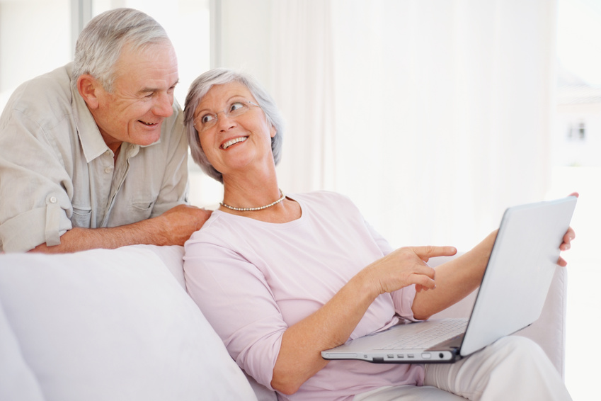 Portrait of a smiling senior woman pointing at the laptop screen to her husband